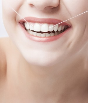 girl-flossing-teeth-close-up