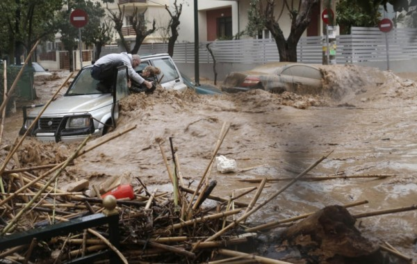 a-man-rescues-a-woman-from-her-car-on-a-flooded-road-in-the-athens-suburb-of-chalandri-in-february1