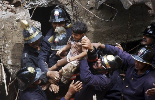 rescue-workers-carry-a-child-who-was-rescued-from-the-rubble-at-the-site-of-a-collapsed-residential-building-in-mumbai-india-in-september