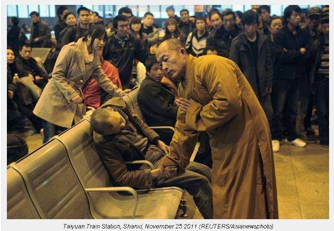 A monk prays for a dead man in the station hall of the Shanxi Taiyuan Train Station, China