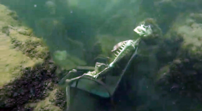 In this frame from video provided by the La Paz Sheriffs' Office, fake skeletons are strategically placed to appear as if they were sitting together with their lawn chairs bound to large rocks in the Colorado River near the Arizona and California border. A man snorkeling came across the two fake skeletons sitting in lawn chairs about 40 feet underwater and reported the skeletons to the La Paz County Sheriff's Office on Monday, May 4, 2015, launching a hunt for what authorities believed could be real bodies. It turned out the skeletons were fake. (AP Photo/La Paz Sheriff's Office)