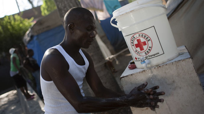 "A man washes his hands with a solution of water and bleach provided by the Haitian Red Cross at Theatre National tent camp in downtown Port-au-Prince November 20, 2010. The United Nations-led international response to Haiti's deadly cholera epidemic is ""inadequate"" and woefully short of funding, aid groups, including the U.N. humanitarian agency, said on Friday. REUTERS/Allison Shelley (HAITI - Tags: DISASTER HEALTH) - RTXUUKO"