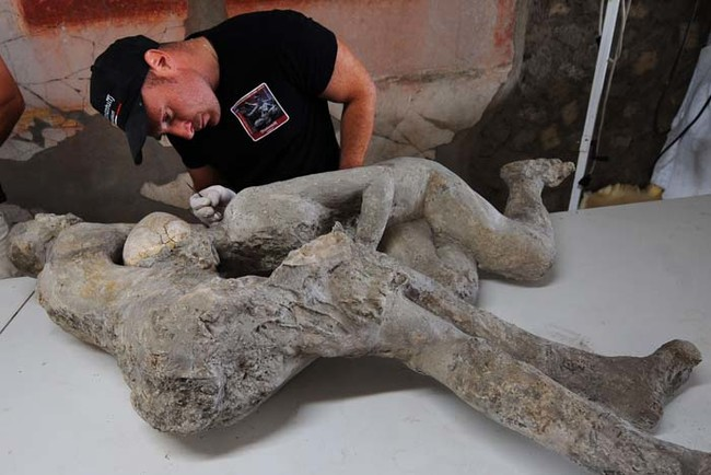A restorer works on a petrified victim of the eruption of Vesuvius volcano in 79 BC, as part of the restoration work and the study of 86 casts in the laboratory of Pompeii Archaeological Site, on May 20, 2015 in Pompeii. AFP PHOTO / MARIO LAPORTA (Photo credit should read MARIO LAPORTA/AFP/Getty Images)