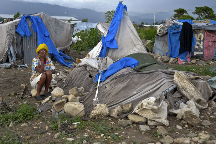 A Haitian woman living in a tent camp for people affected by the January 2010 earthquake covers her face as she reacts after her tent home was destroyed by Tropical Storm Isaac outside of Port-au-Prince August 26, 2012. Tropical Storm Isaac left six dead in Haiti, still recovering from a 2010 earthquake, and at least three missing in the Dominican Republic after battering their shared island of Hispaniola on Saturday. REUTERS/Swoan Parker (HAITI - Tags: DISASTER SOCIETY ENVIRONMENT) - RTR3757J