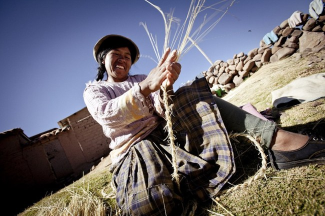 CUZCO, PERU: Female villager in the initial stages of rope making. TAKING handy-craft to a new level pictures show a five century-old tradition where local people build the ultimate hand-made 100-foot-long rope bridge. One thousand villagers come together in a three-day feat in taking down the old Queswachaca Bridge and making a new one, with a grand celebration on the fourth day. This bridge is the only bridge conserved of this type from the Inca tradition. Working up to twelve hours-a-day, pictures show the construction stages from making the smaller ropes and then braiding them into the huge ropes needed to make the bridge over the river Apurimac, in the Cuzco region of Peru.