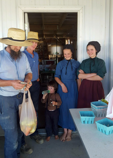 Sarah Hershberger, second from right, is pictured at her family's roadside stand in Homer Township on Sept. 24. Also pictured are her father and three of her siblings. (PHOTO PROVIDED BY 1851 CENTER FOR CONSTITUTIONAL LAW)