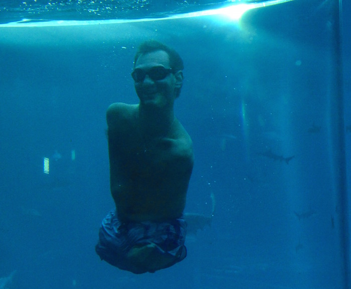 Australian motivational speaker, Nick Vujicic, who was born without limbs, swims in a shark habitat while protected within a customised acrylic enclosure at Marine Life Park, Resort World Sentosa in Singapore on September 5, 2013. Vujicic is in Singapore for a one-day event where he will be speaking to a 5,000 strong audience. AFP PHOTO / ROSLAN RAHMAN (Photo credit should read ROSLAN RAHMAN/AFP/Getty Images)