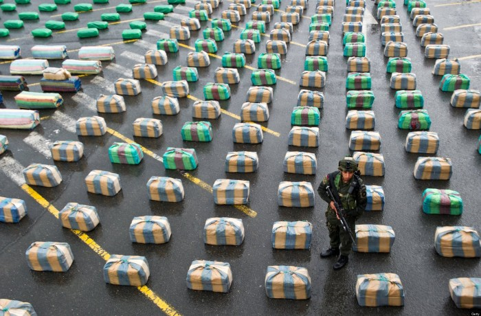 "A Colombian member of a police anti-drugs unit stands guard next to marijuana packages displayed to the press, on March 26, 2013, in Cali, department of Valle del Cauca, Colombia. Police seized 7.7 tons of marijuana during the operation ""Republica 39"", carried out between the municipalities of Tulua and Buga, who belonged to the Revolutionary Armed Forces of Colombia (FARC) guerrillas. The Director General of the National Police of Colombia, General Jose Roberto Leon Riano, said that 80 tons of marijuana and 36 tons of cocaine have been seized so far this year. AFP PHOTO/Luis ROBAYO (Photo credit should read LUIS ROBAYO/AFP/Getty Images)"