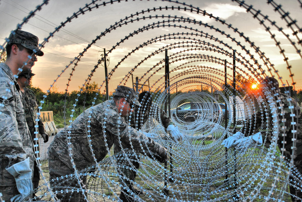 """Airmen from the 621st Contingency Response Wing at McGuire Air Force Base, N.J., construct razor wire fences around their camp perimeter June 24 during a noncombatant evacuation exercise at Mackall Army Airfield, N.C. CRW Airmen manned defensive fighting positions as the exercise scenario became """"hostile."""" (U.S. Air Force photo/Staff Sgt. Nicholas Phelps)"""