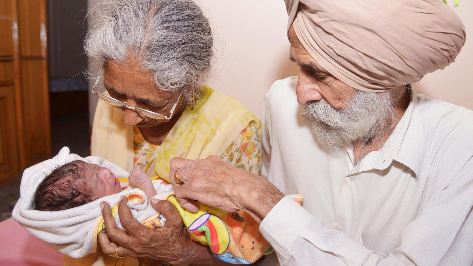 Indian parents Mohinder Singh Gill (R), 79, and Daljinder Kaur, 70, pose for a photograph as they hold their newborn baby boy Arman at their home in Amritsar on May 11, 2016. An Indian woman who gave birth at the age of 70 said May 10 she was not too old to become a first-time mother, adding that her life was now complete. Daljinder Kaur gave birth last month to a boy following two years of IVF treatment at a fertility clinic in the northern state of Haryana with her 79-year-old husband. / AFP / NARINDER NANU (Photo credit should read NARINDER NANU/AFP/Getty Images)