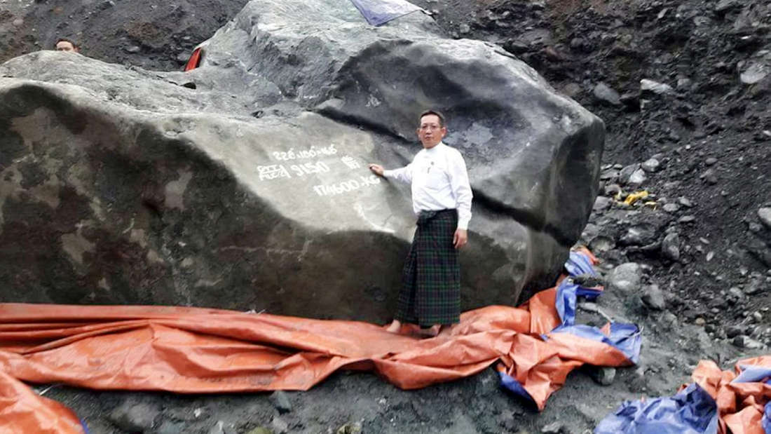 Stunned miners thought they had won the lottery when they struck this enormous boulder - the world's most valuable piece of JADE worth $175m. See SWNS story SWJADE. Workers were excavating rare gems at a remote mine in Kachin State, Burma, when they stumbled across the huge jadeite rock on Thursday afternoon. It weighs a staggering 175 tonnes (174,600kg) , measures 9ft high, 18ft long and 18ft wide. Remarkable pictures show local politician U Tint Soe standing next to the giant gem as it towers above him. The rock - which will appear its distinctive green once cleaned - is second only in size to the a carved statue at the Jade Buddha Palace in China which weighs 260 tonnes.
