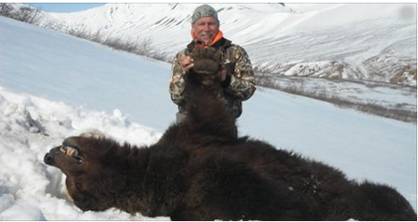 This Man Posed Proudly With the Bear he Shot While it Was Hibernating